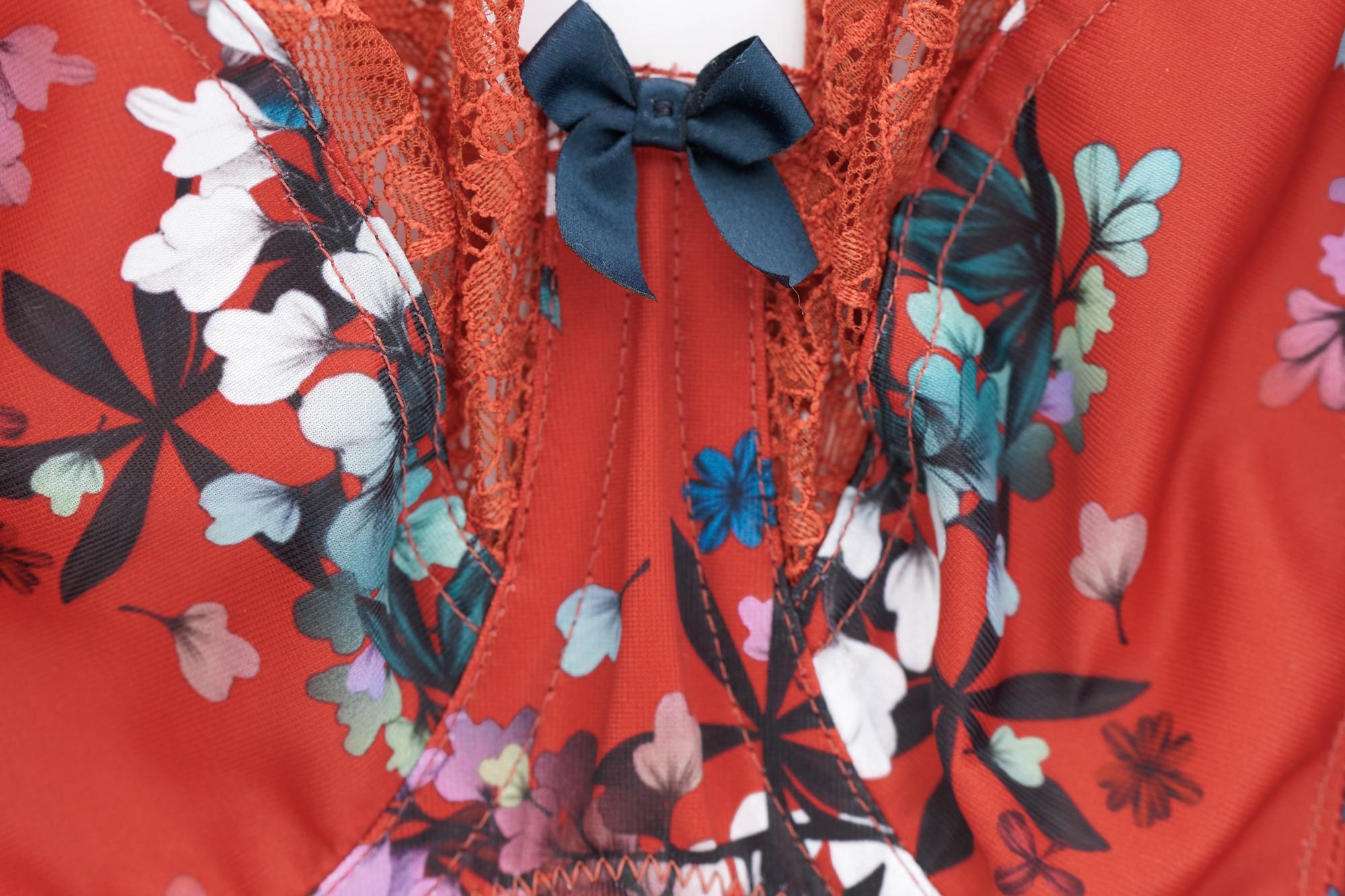 Biustonosz Chi Chi marki Sculptresse w wersji red floral (czerwony w kwiaty) - zbliżenie na mostek i kokardkę